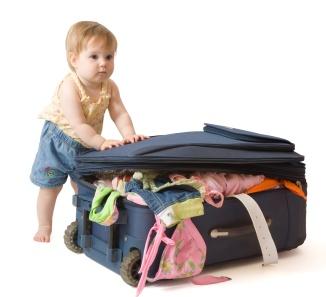 Baby girl standing near the suitcase, trying to pack it, isolated, with clipping path